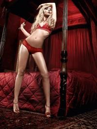 Nyitott formavilágú nyakpántos csipke-melltartóból és tüll boyshortból álló vörös bikini-együttes.